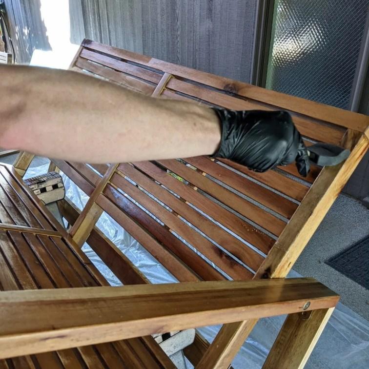 Applying teak oil to acacia wood patio furniture with foam brush