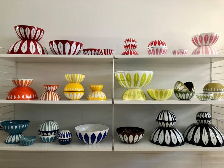 Cathrineholm bowls in multiple sizes and colors displayed on shelves - photo by Alexa Greaves