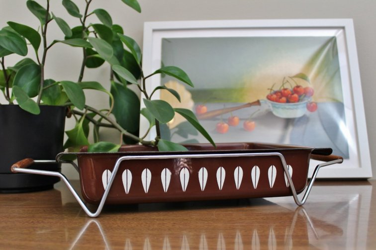 Cathrineholm brown and white lotus lasagna pan with stand in front of mid-century painting