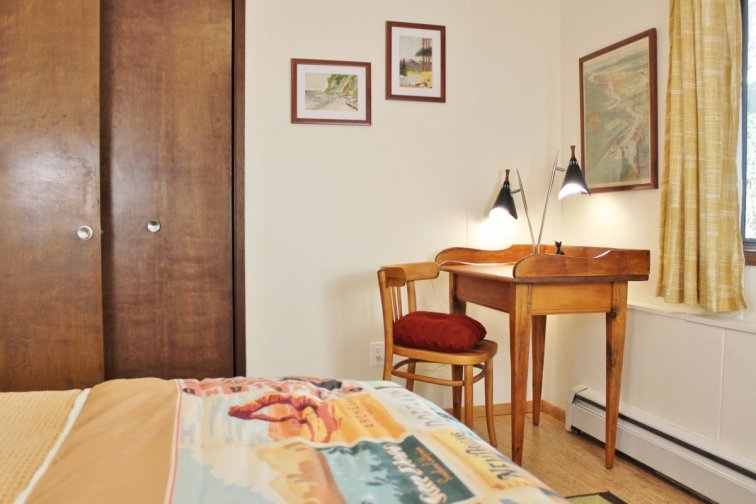 Travel-themed guest room with writing desk and lamp