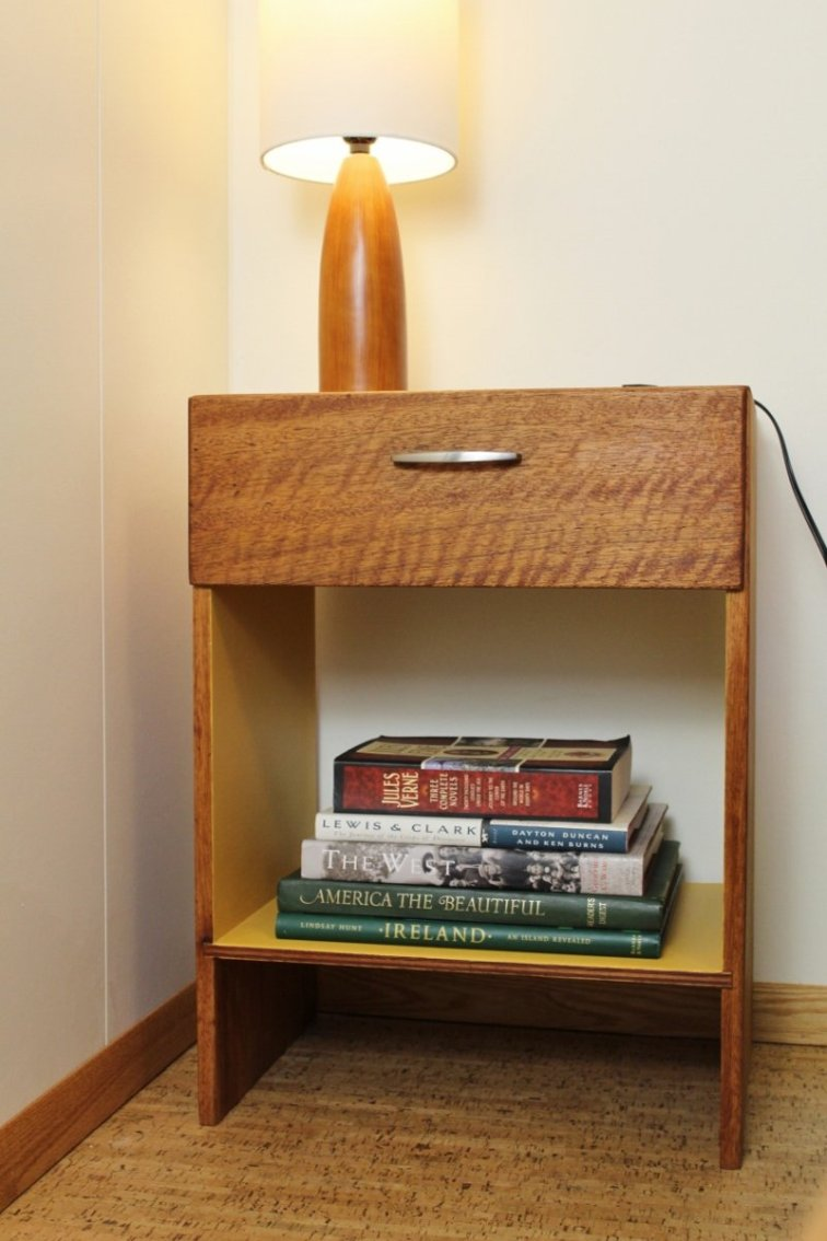 Mid-century modern nightstand with stack of travel books