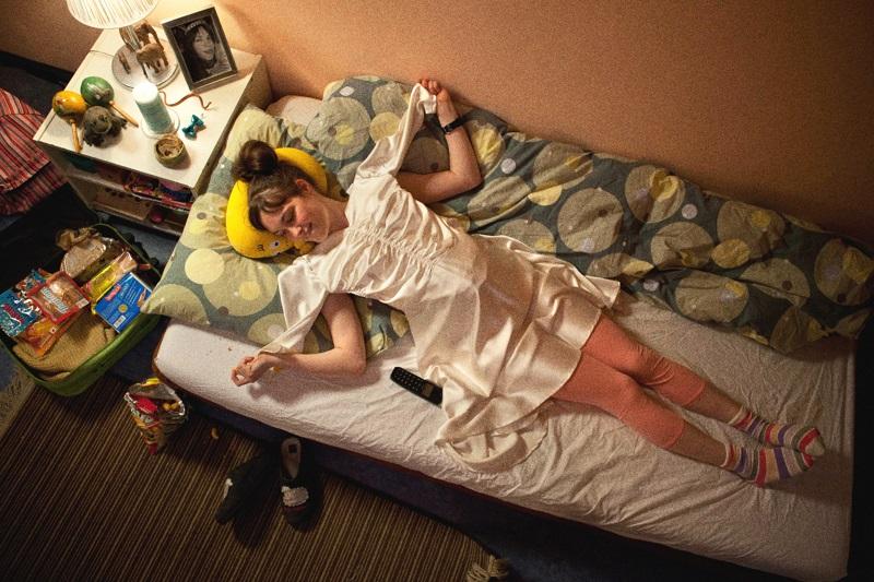 Dora Sitzt bereit für die Reise auf dem Bett, sie telefoniert mit Felix