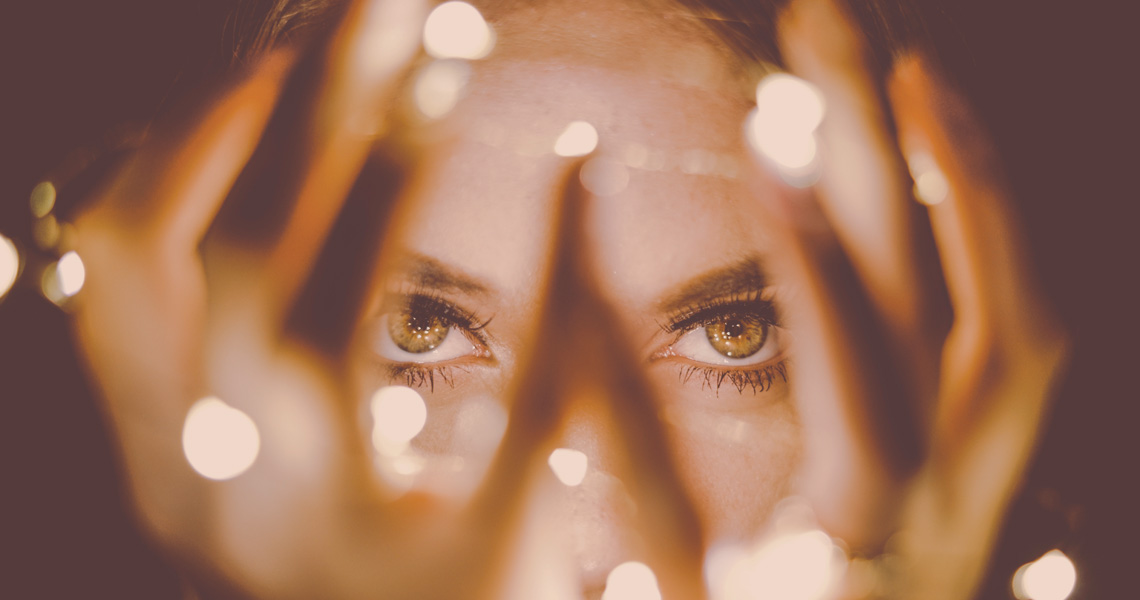 A woman's eyes, seen through her fingers that are holding tiny fairy lights - Post-bereavement hallucinations