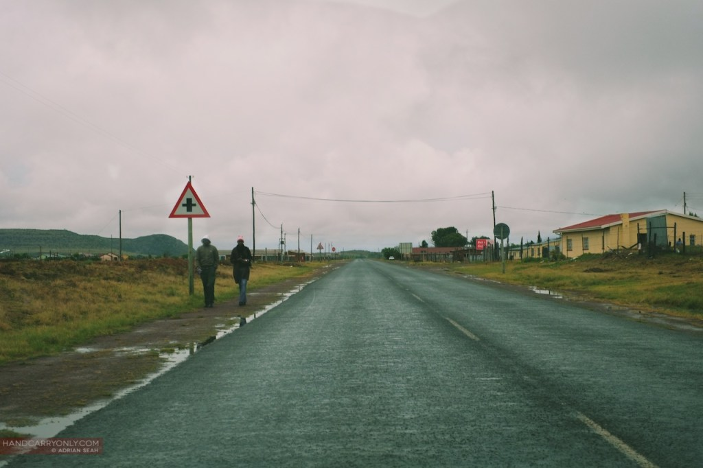 2 figures walking along a largely deserted road south africa