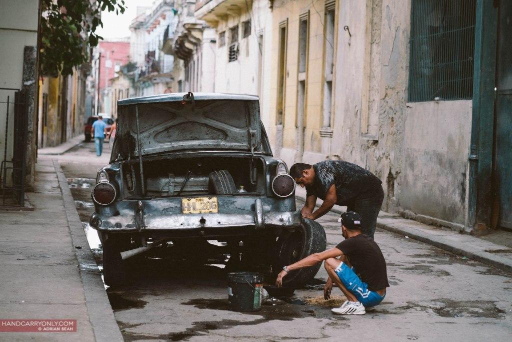 two men fixing an old classic car in havana cuba