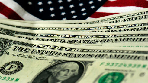Dollar-Scheine vor amerikanischer Flagge: Der Greenback wird immer stärker, die Geldpolitik der Fed unsicherer. Quelle: SAP/dpa