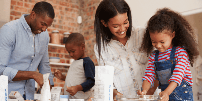 Family baking together and laughing in post called parenting as a team: using humor to deflect tension