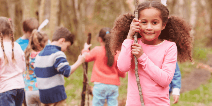 girl holding stick in adventure play setting in post about helping power struggles