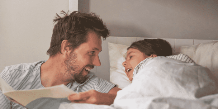 Father and child laughing at bedtime story