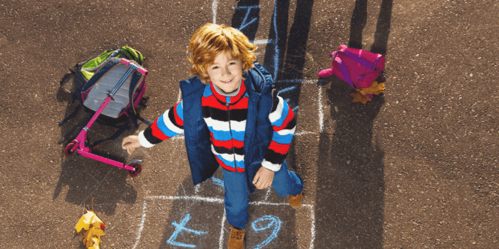 Boy looking happy playing hopscotch