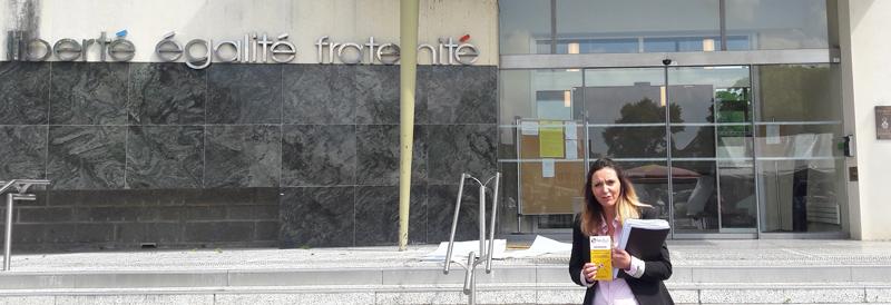 Photo d'illustration. Devant la Mairie de Saint-Lo, la conseillère en insertion d'Handiuni se tient debout. On peut lire la devise Liberte-Égalite-Fraternitésur la facade.