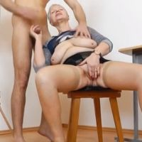 Granny Teacher masturbates while giving a handjob