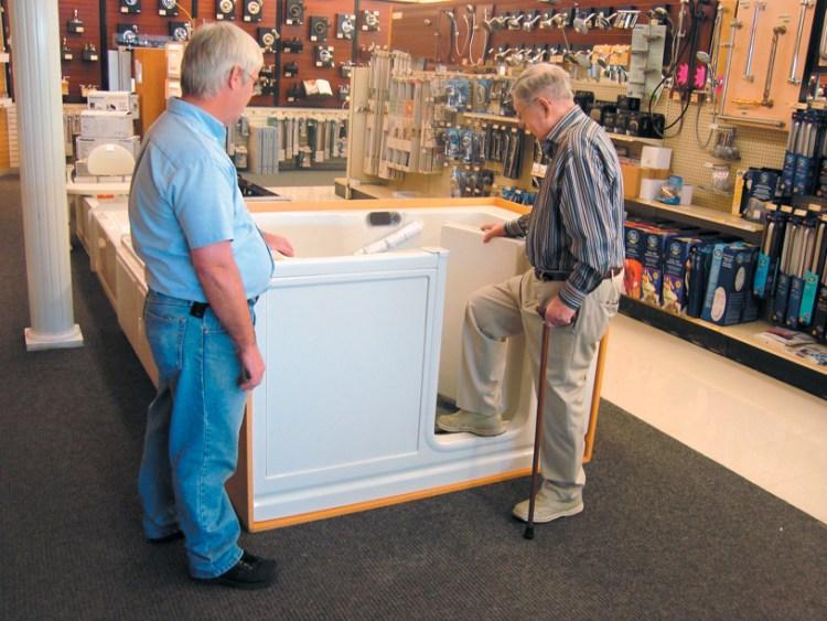 Elderly man stepping into walk in tub