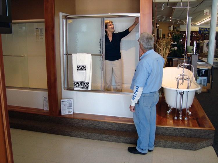 Customer standing inside sterling tub shower