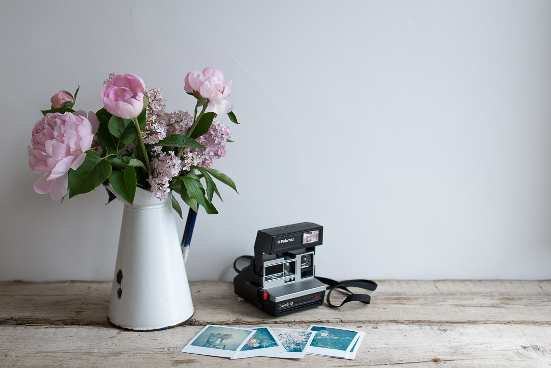 Polaroid camera and peonies. Instant film photography