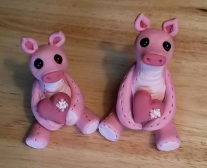 """Two """"Pig with a Heart"""" sculptures made of polymer clay and glass beads"""