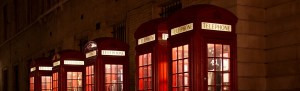 A row of lighted red telephone booths by the sidewalk.