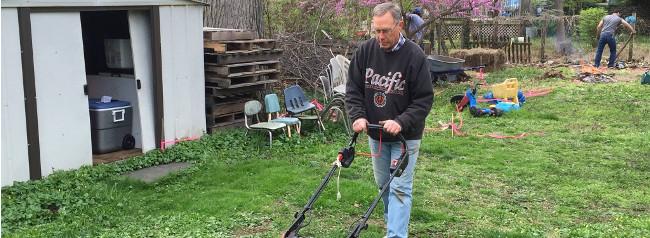 photo: man mowing grass