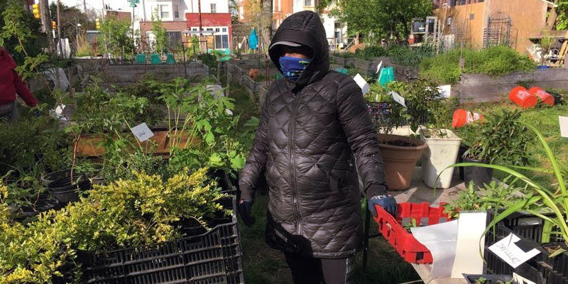 photo: heavily bundled woman with plants