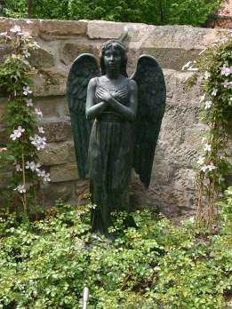 Die Engelfigur bewacht den Garten dezent und ist doch ein Blickfang.