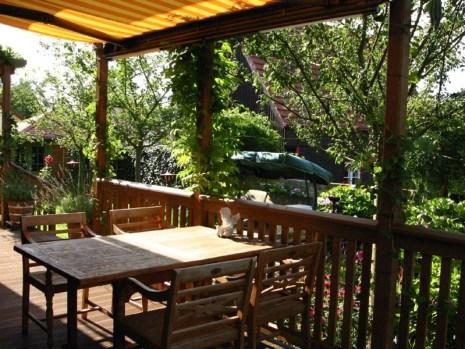 Die höher gelegende rund um das Haus verlaufende Veranda bietet einen sehr geschützten, sonnigen Sitzplatz mit Blick in den Bauerngarten.