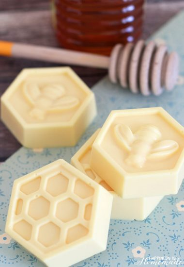 Yellow honeycomb shaped milk and honey soaps on a blue background with wooden honey dipper in background