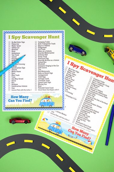 "Two road trip ""I Spy Scavenger Hunt"" printable game cards on green background with road graphic and small toy cars"