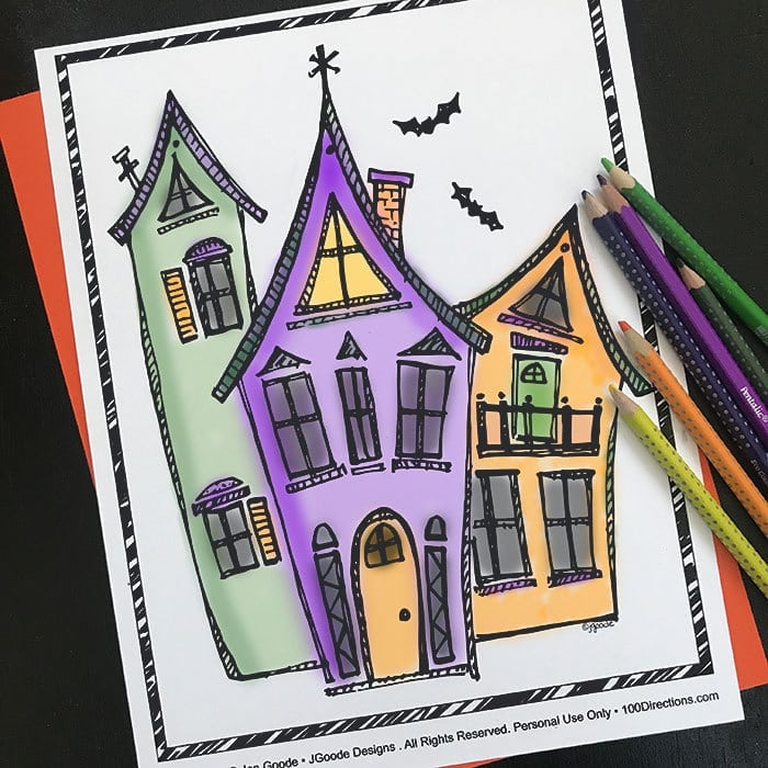 Haunted house coloring page with bats and colored pencils