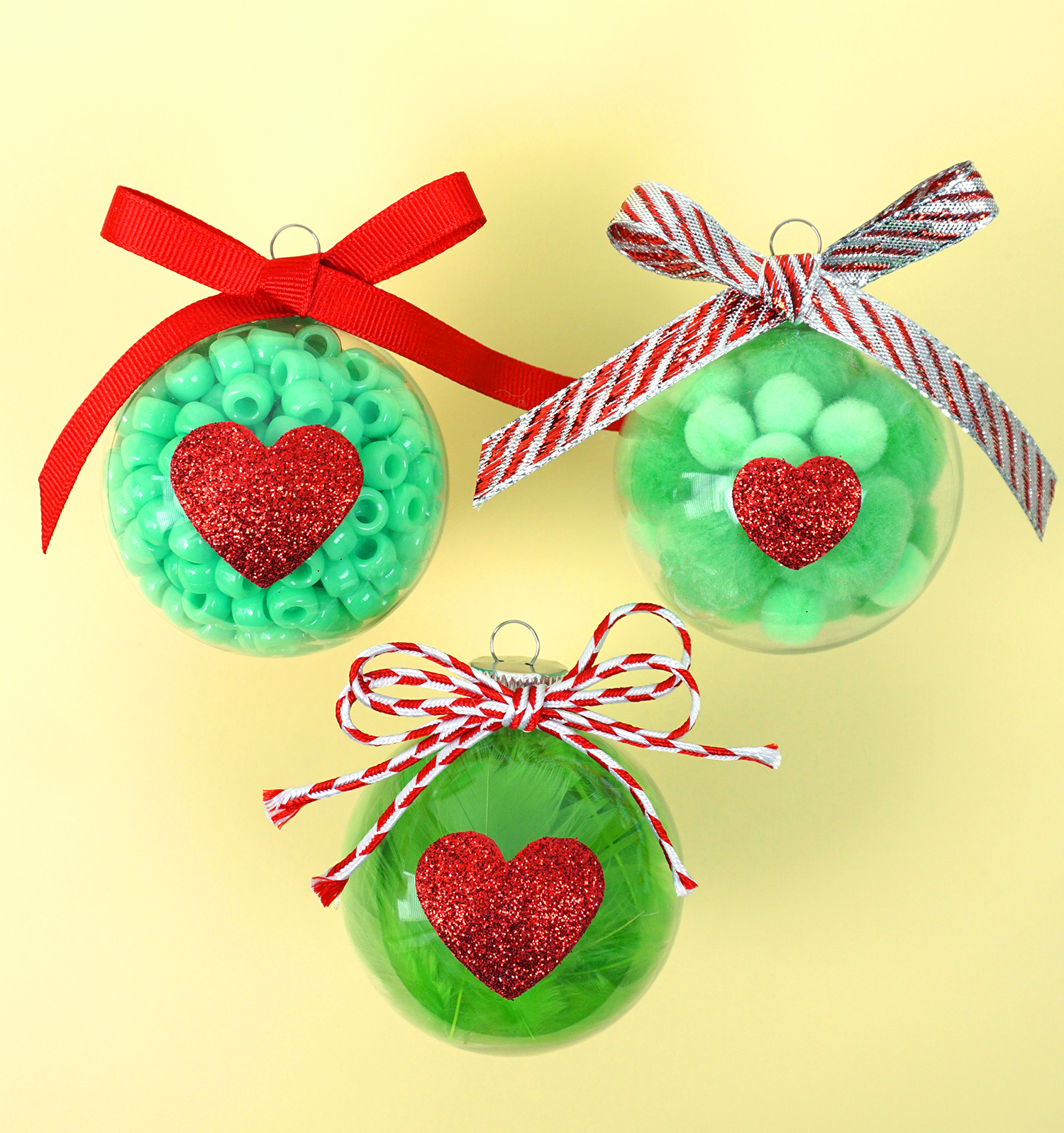 Grinch Ornaments: easy Christmas craft for kids. 3 Green ornaments with red hearts on yellow background.