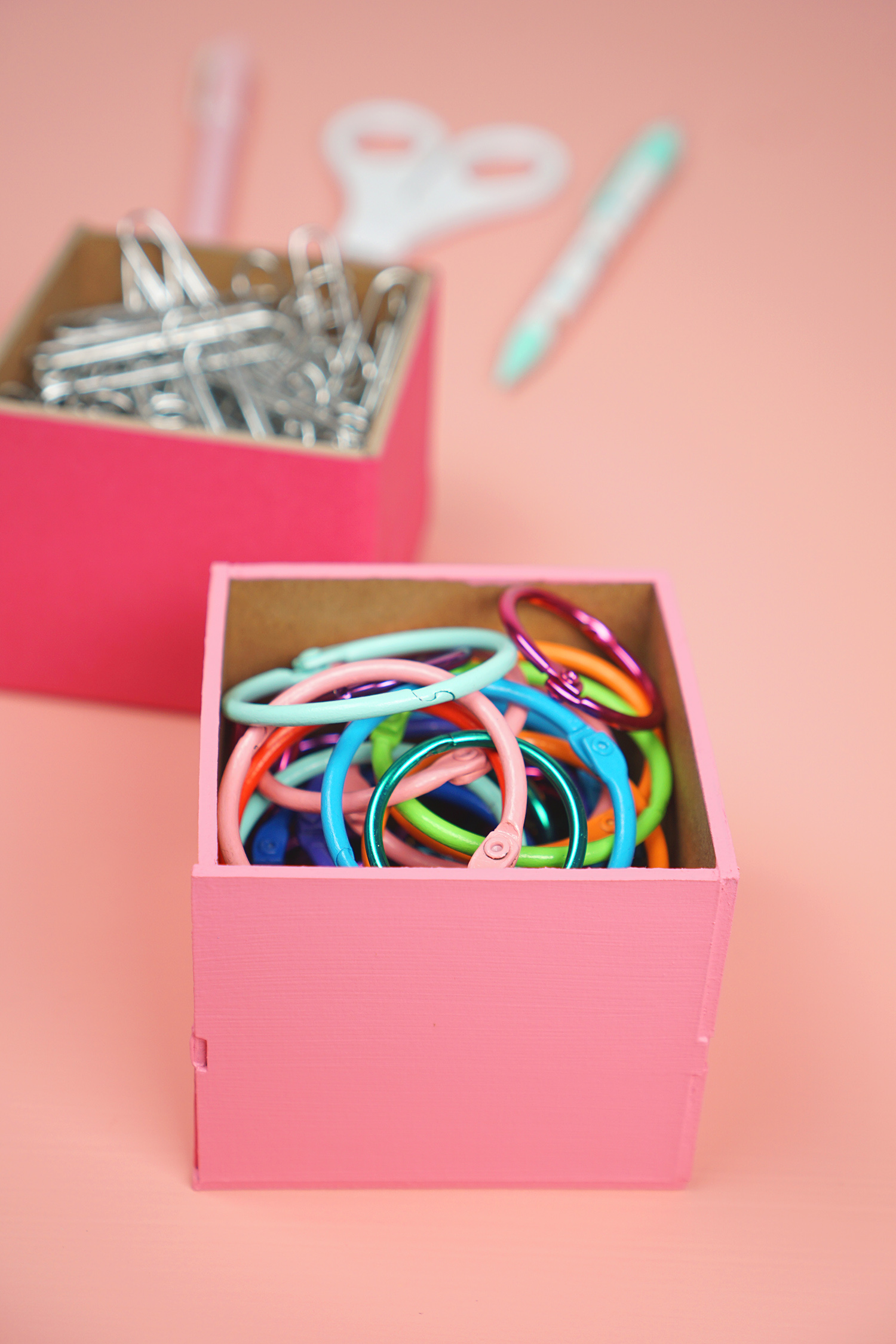 Pink desk organizer box filled with colorful binder rings and office supplies