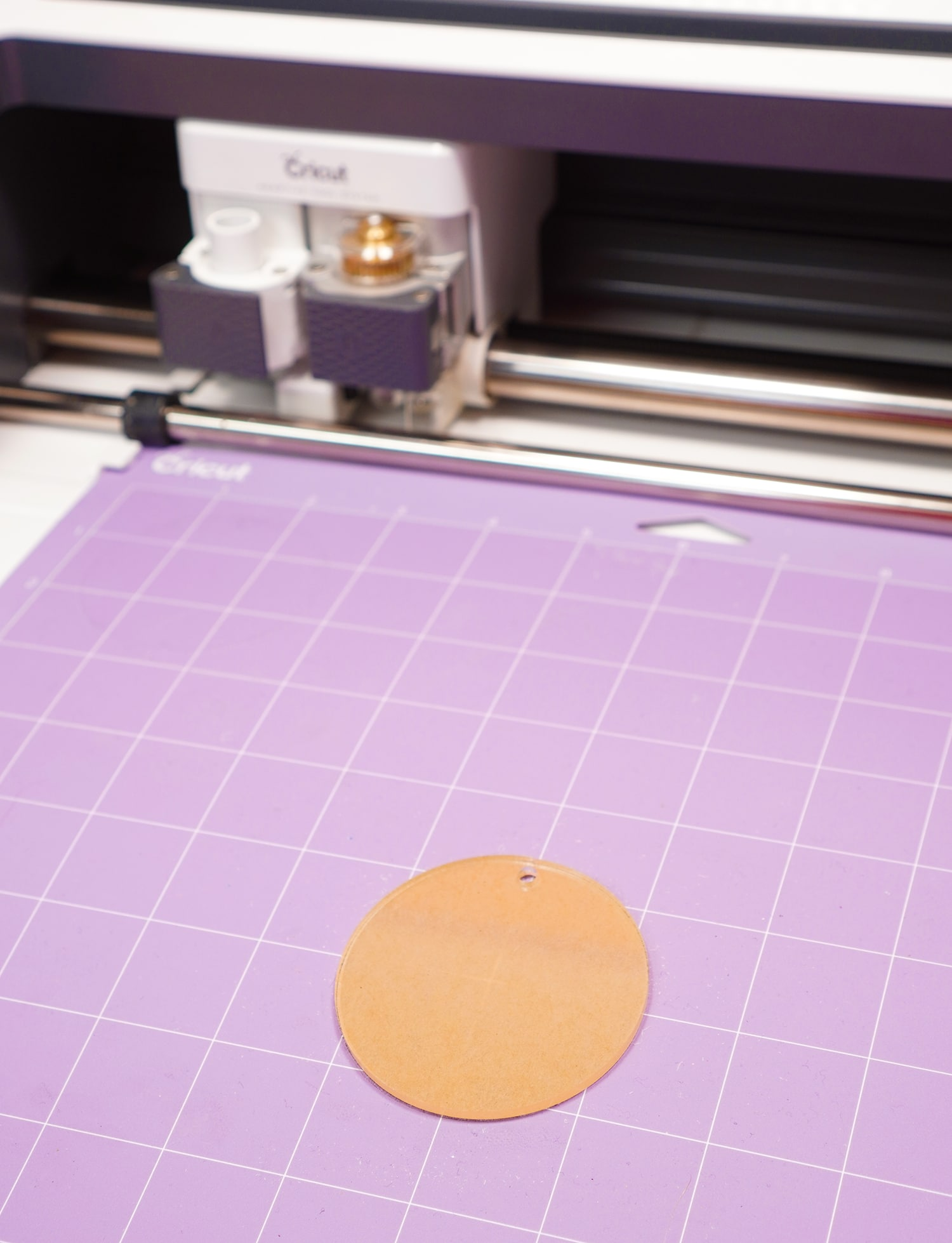 Acrylic keychain blank in the center of a purple StrongGrip Cricut mat