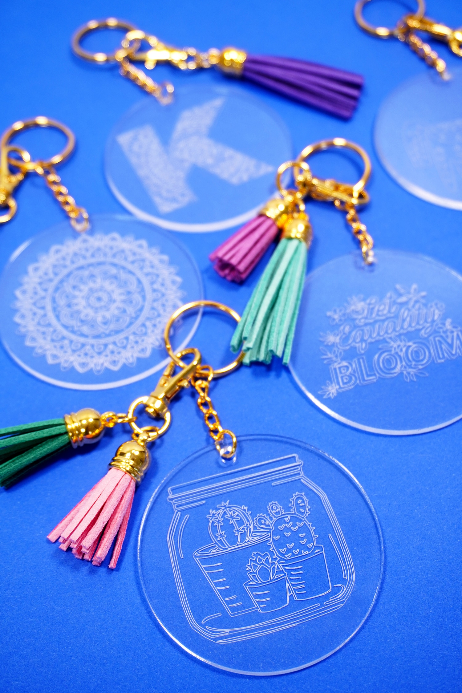 Engraved acrylic keychains with tassels on a blue background made with Cricut Maker Engraving Tool