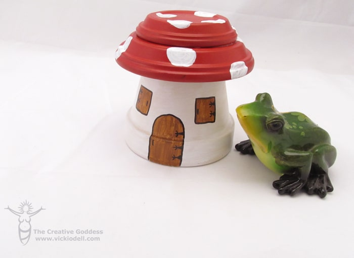 flower pot shaped fairy garden house painted to look like mushroom with red and white polka dot top with a green ceramic frog next to it