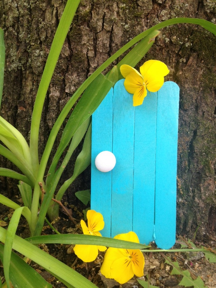 Fairy garden door made from popsicle sticks and painted light blue with yellow flowers on it