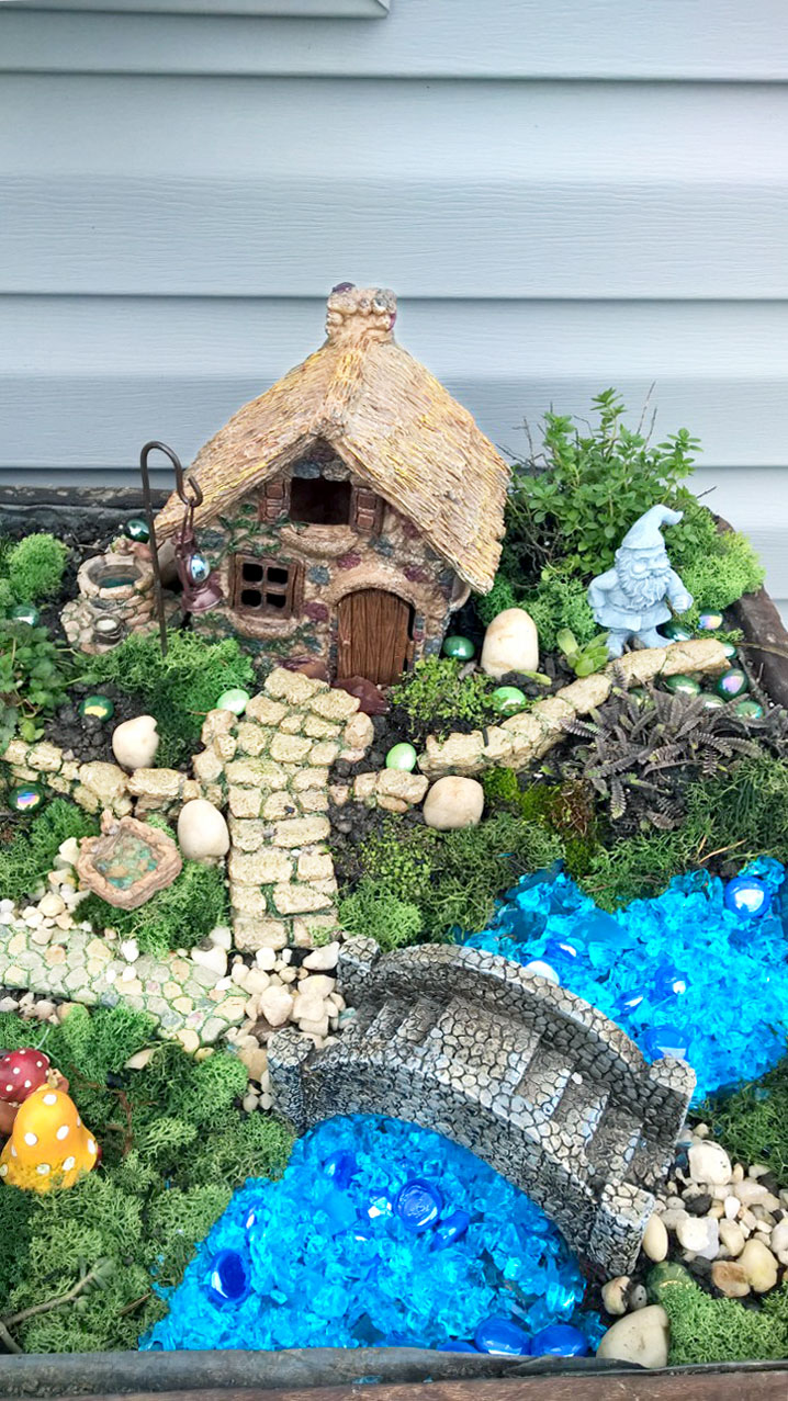 Fairy garden cottage in planter with greenery, rock bridge, and blue stones to simulate water