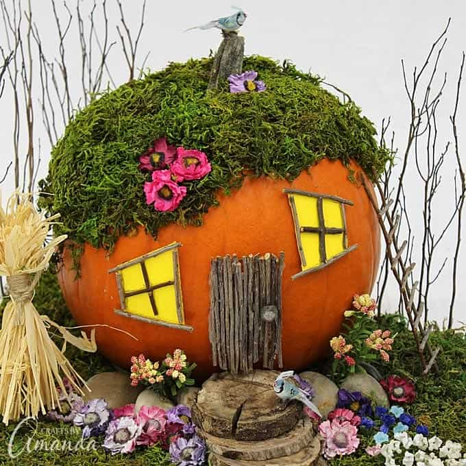 Orange pumpkin turned into a fairy garden house with a moss roof and wooden stick made door surrounded by flowers and greenery