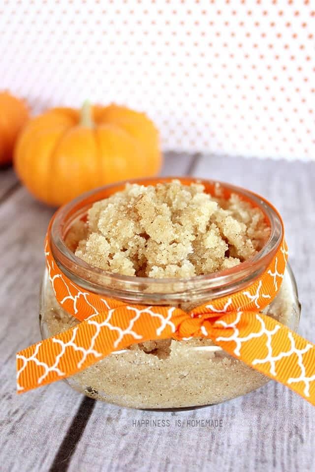 A glass jar of vanilla pumpkin spice sugar scrub with an orange bow on a wood background with a mini pumpkin