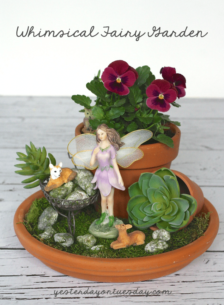 Red flowers in terra cotta pot with fairy figurine in front and greenery with small animal figurines