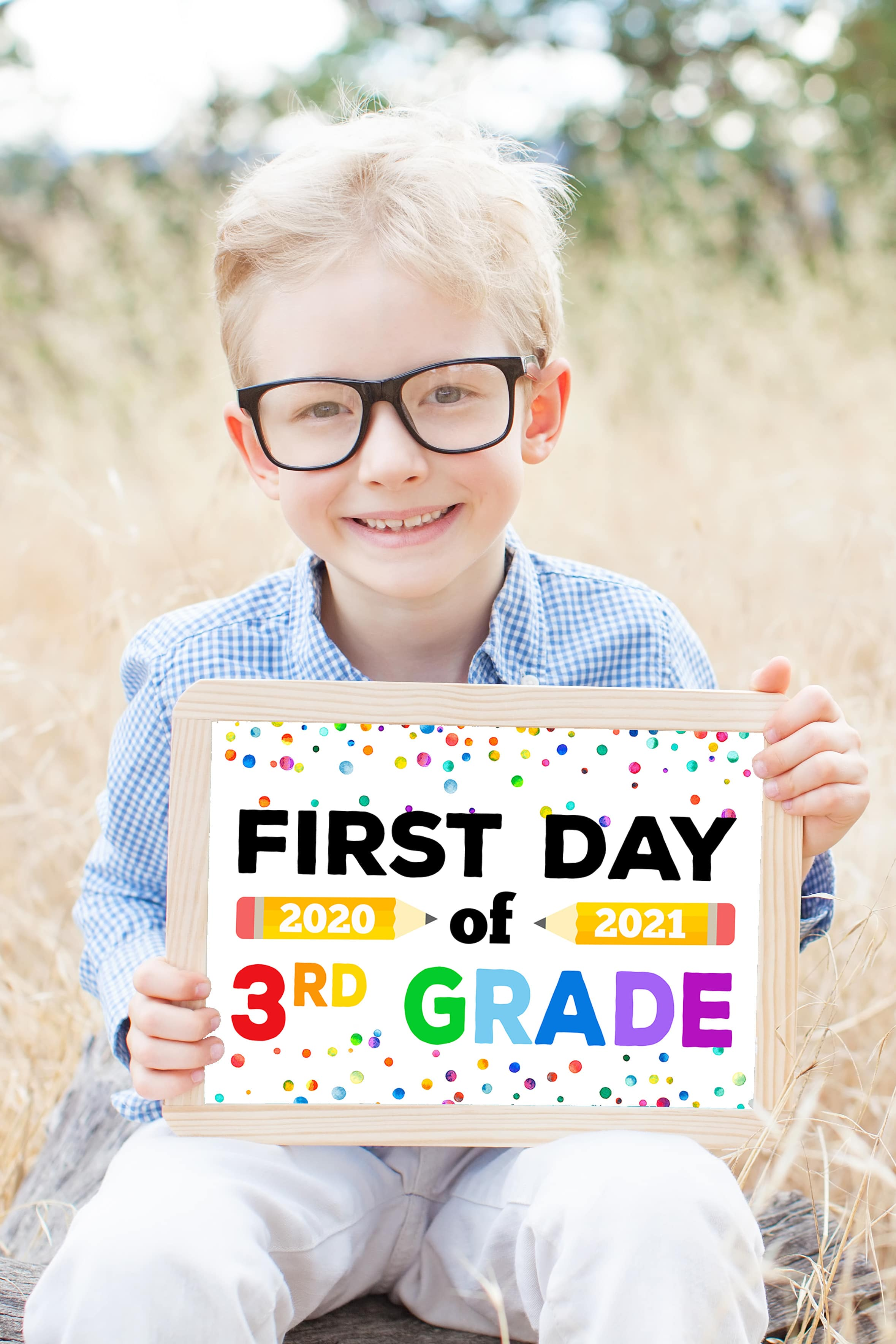 "Boy in glasses holding ""First Day of 3rd Grade 2020-21"" sign."