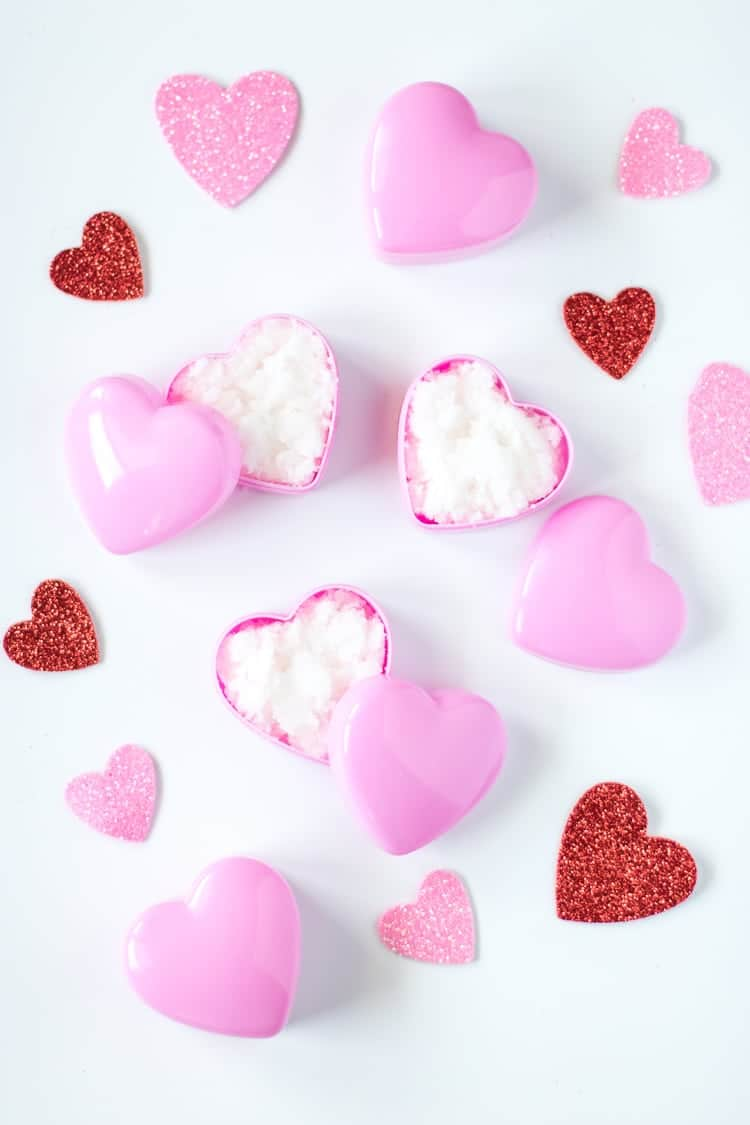 Heart jars of sugar lip scrub on a white background with glittery red hearts