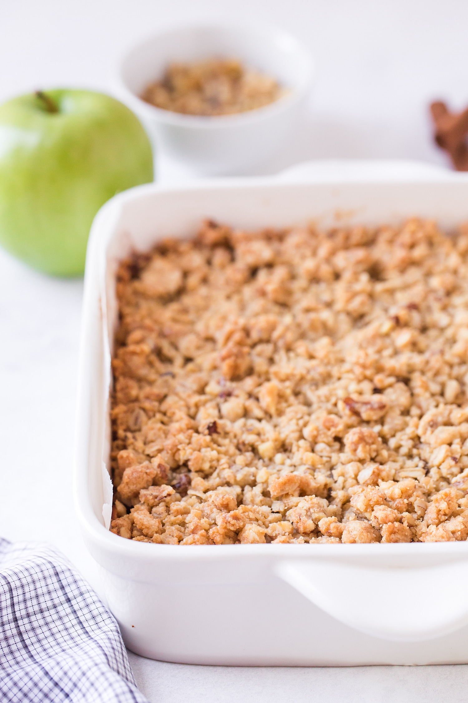 Apple pie bars in white baking dish with green apples in background