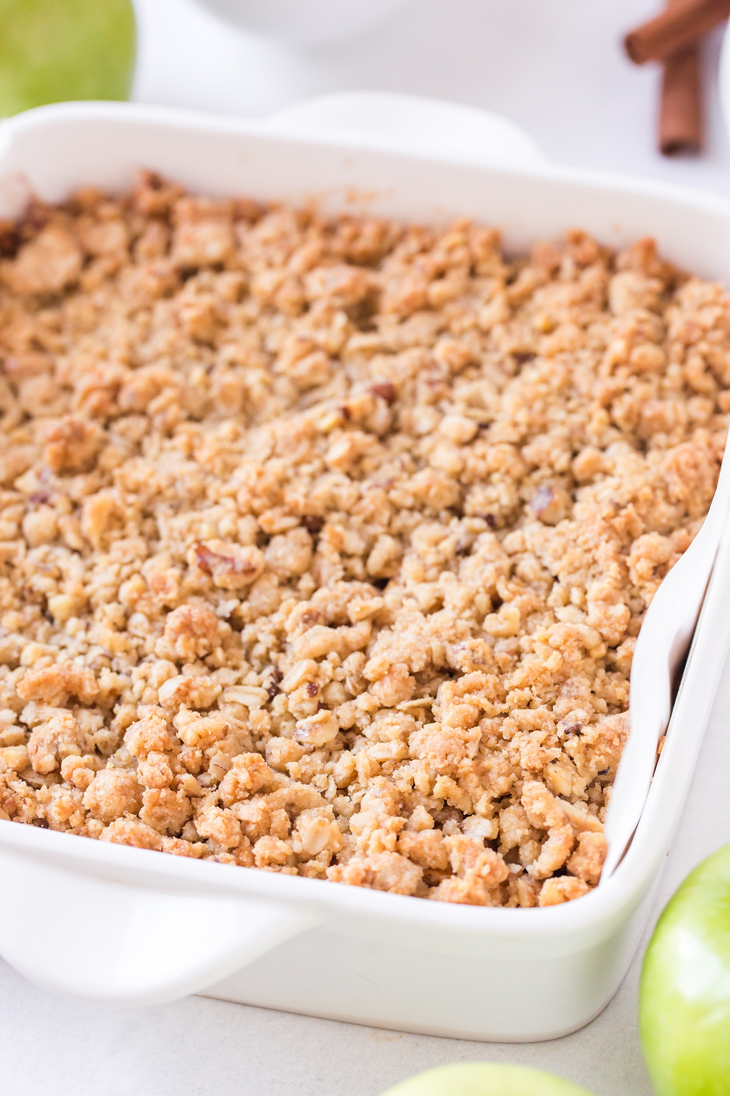 Close up of streusel topping on apple pie bars in white baking dish