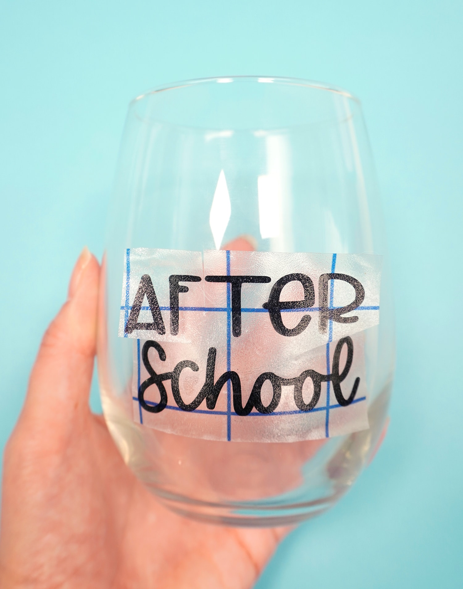 "Hand holding stemless wine glass with ""After School"" vinyl transfer"