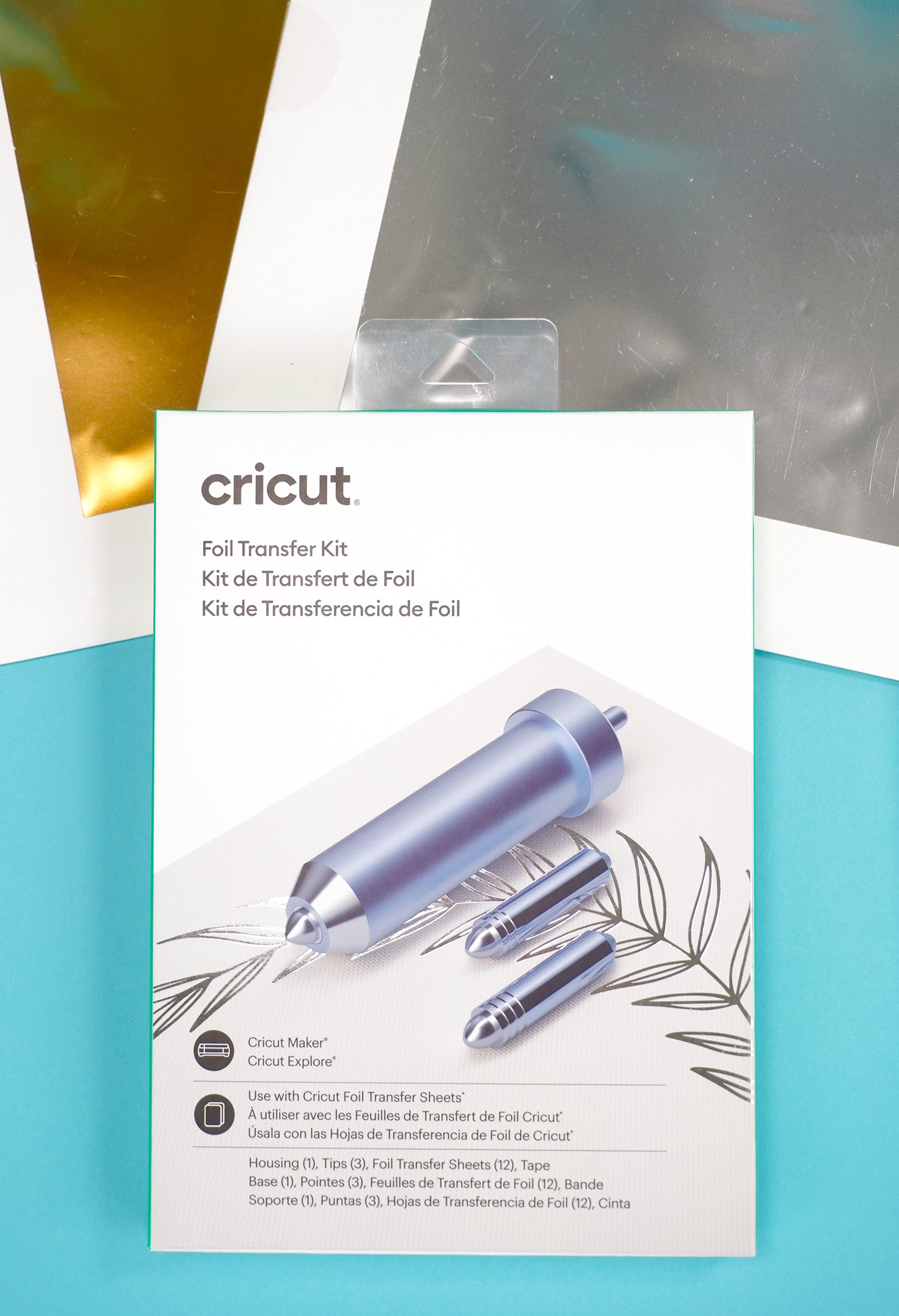 Cricut Foil Transfer Kit packaging and gold and silver foil on blue background