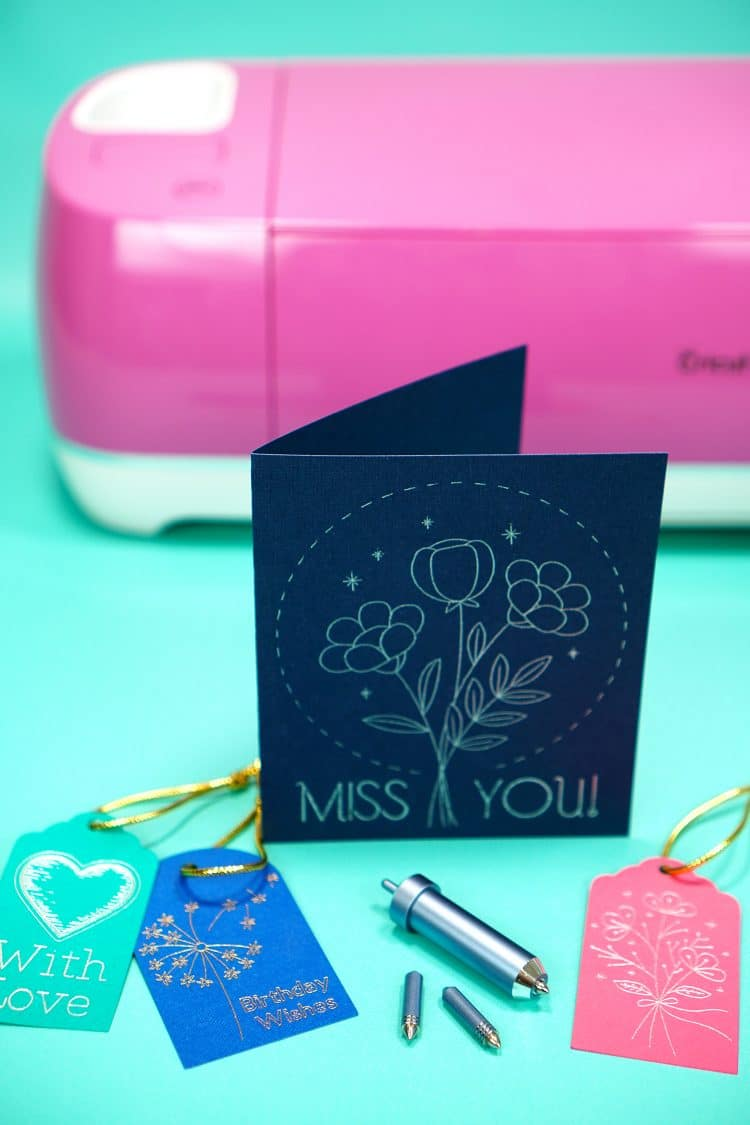 Colorful cards and gift tags with Cricut Foil Transfer System Tools and pink Explore Air 2 on teal background