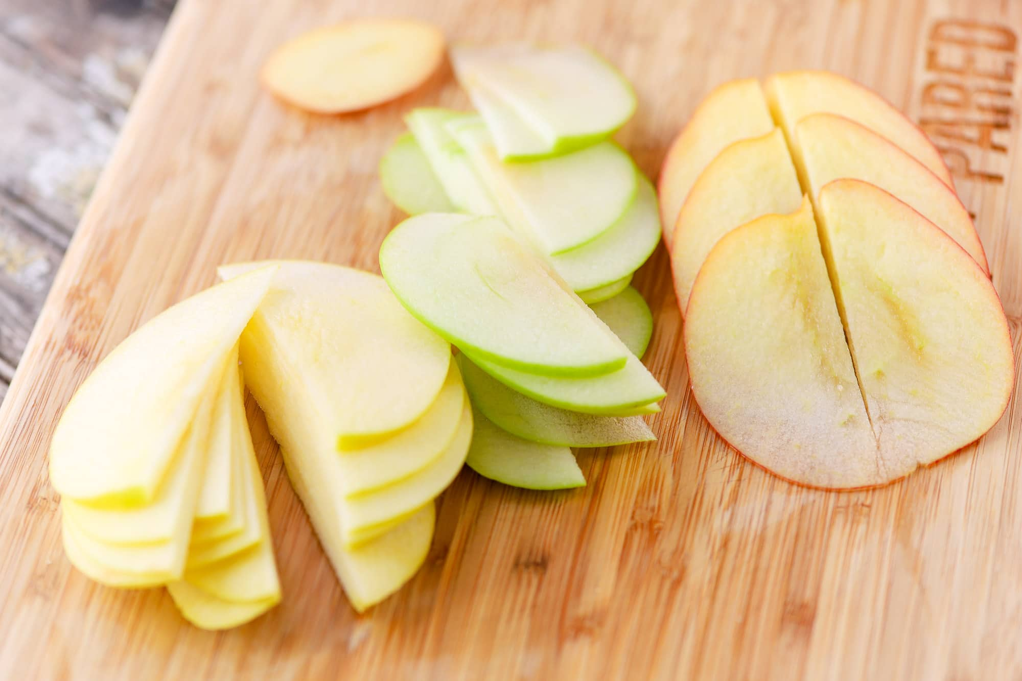 Red, Yellow, and Green Apple Slices on a Wood Cutting Board
