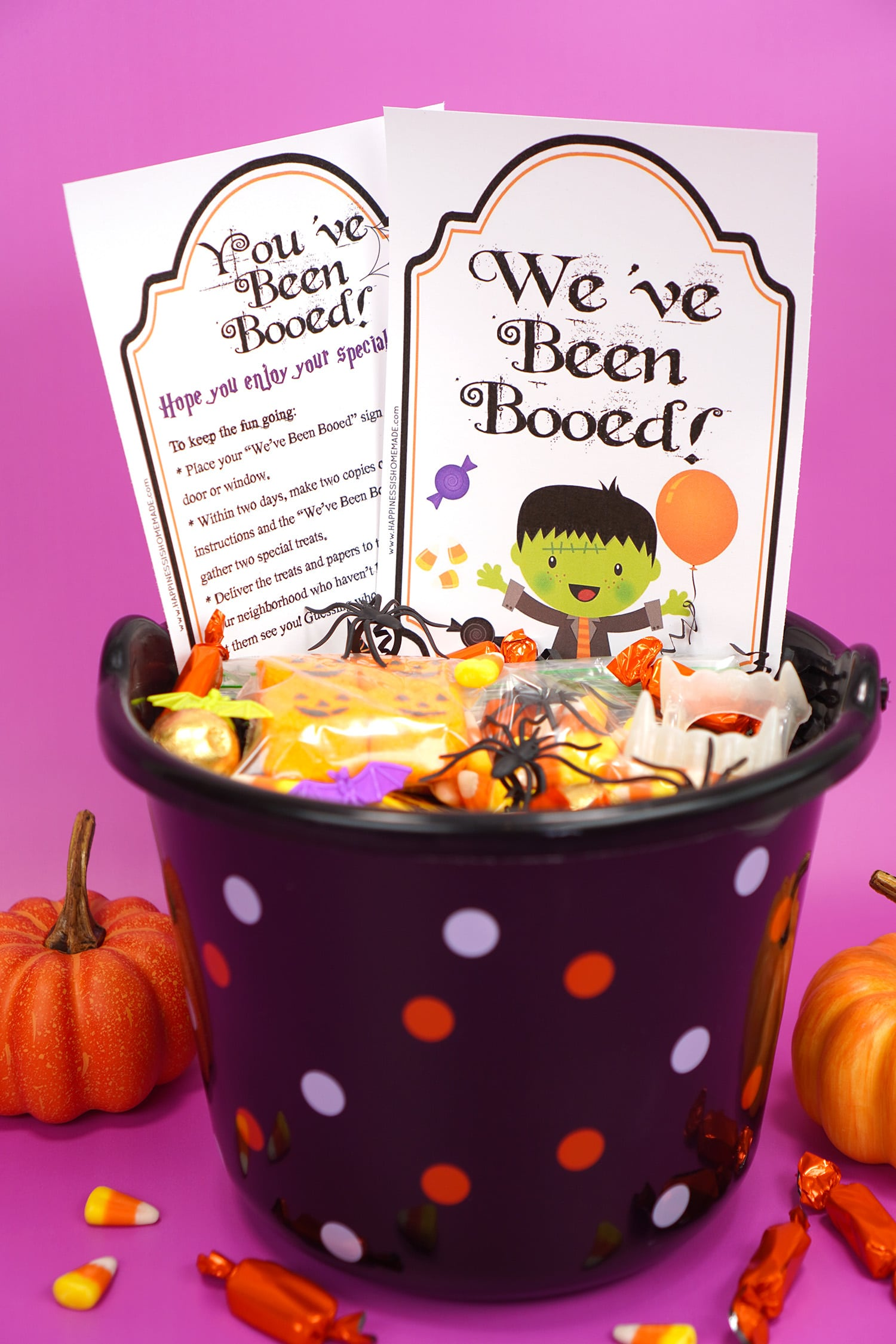 """Boo Basket filled with Hallowen candy and novelty toys with """"You've Been Booed""""and """" We've Been Booed"""" printable signs on purple background with pumpkins and candy corn"""