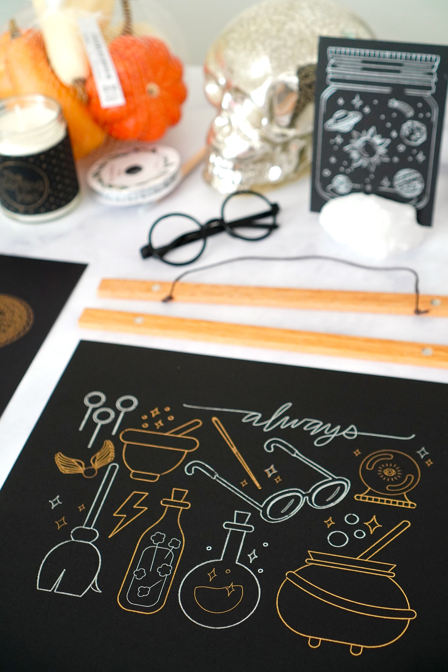 Harry Potter inspired gold and silver foil artwork on table with picture hangers and Halloween props
