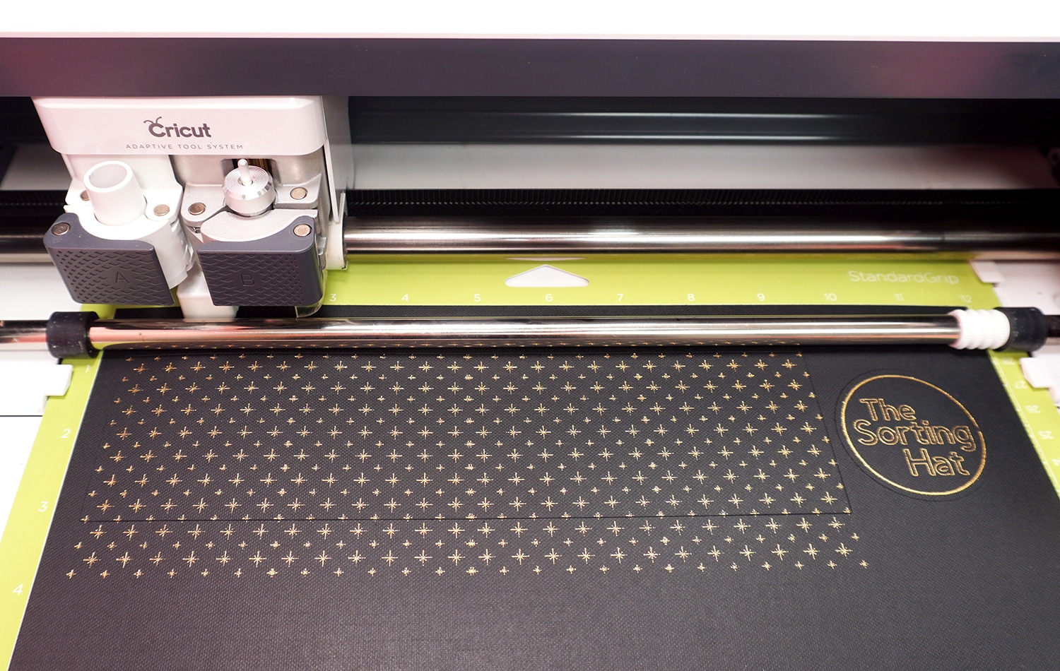 """Gold foiled star design and """"The Sorting Hat"""" label on black cardstock in Cricut Maker machine"""