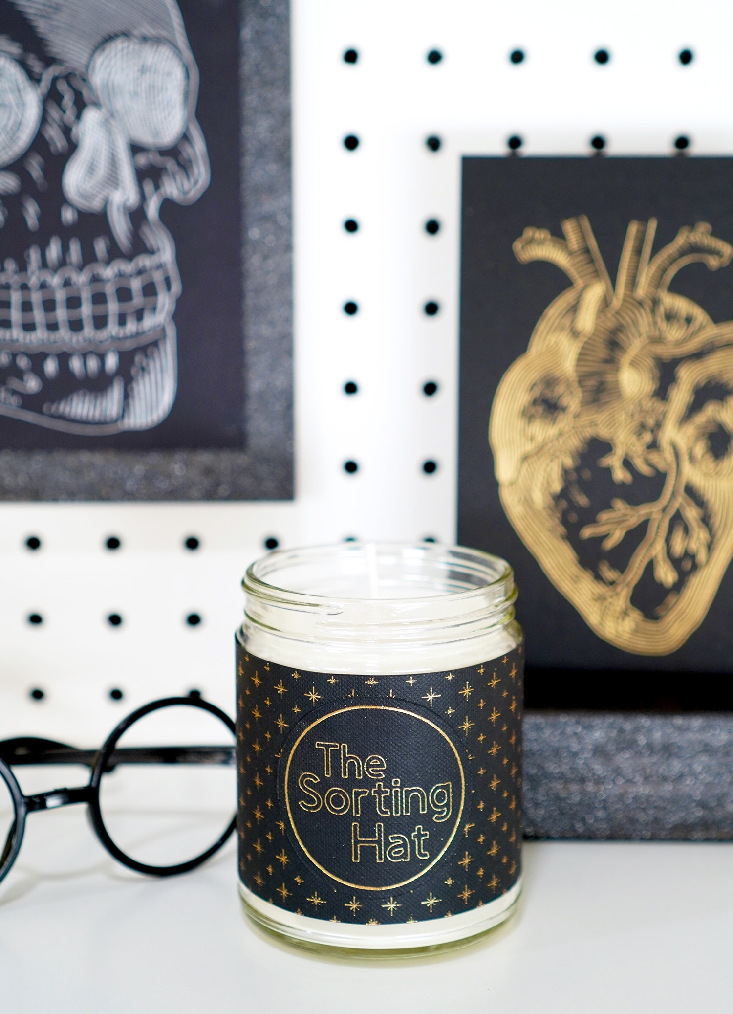"""""""The Sorting Hat"""" candle with black label with gold stars with Harry Potter glasses, foil skull and anatomical heart prints in background"""